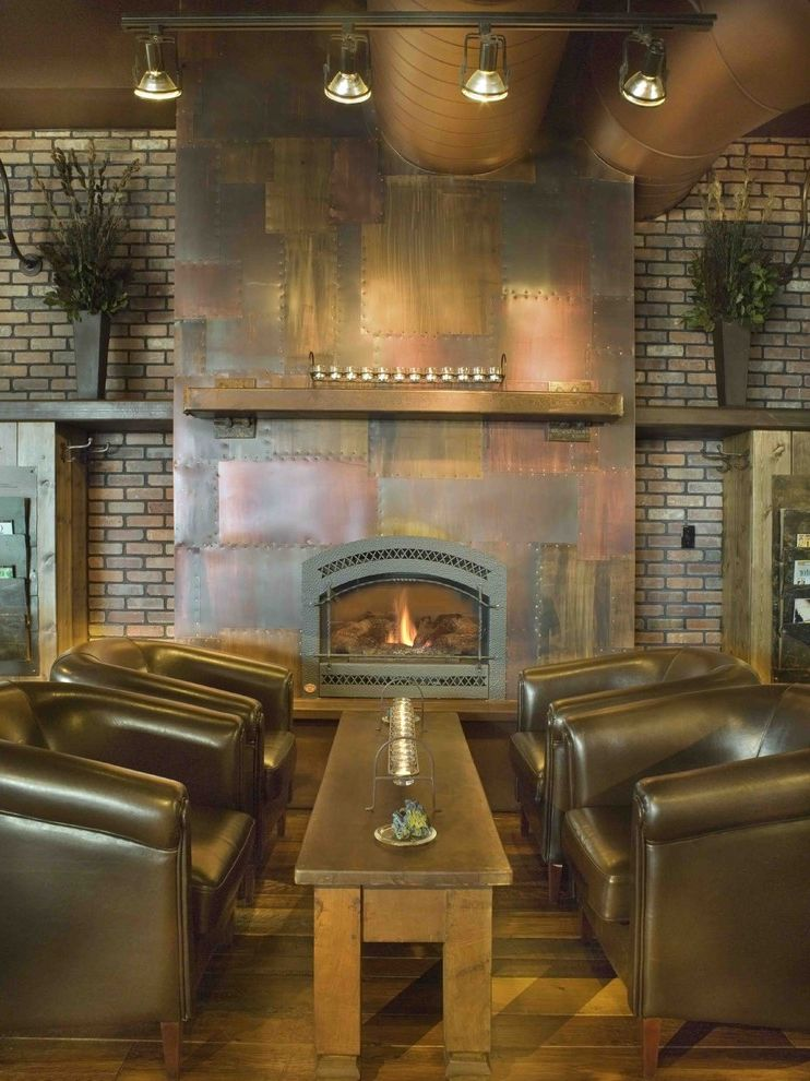 Sheet Metal Homes with Rustic Living Room  and Brass Brick Wall Bronze Copper Exposed Ducting Fireplace Leather Armchairs Lofted Ceilings Mantle Riveted Metal Fireplace Surround Rustic Track Lighting Wood Bench Wood Floor