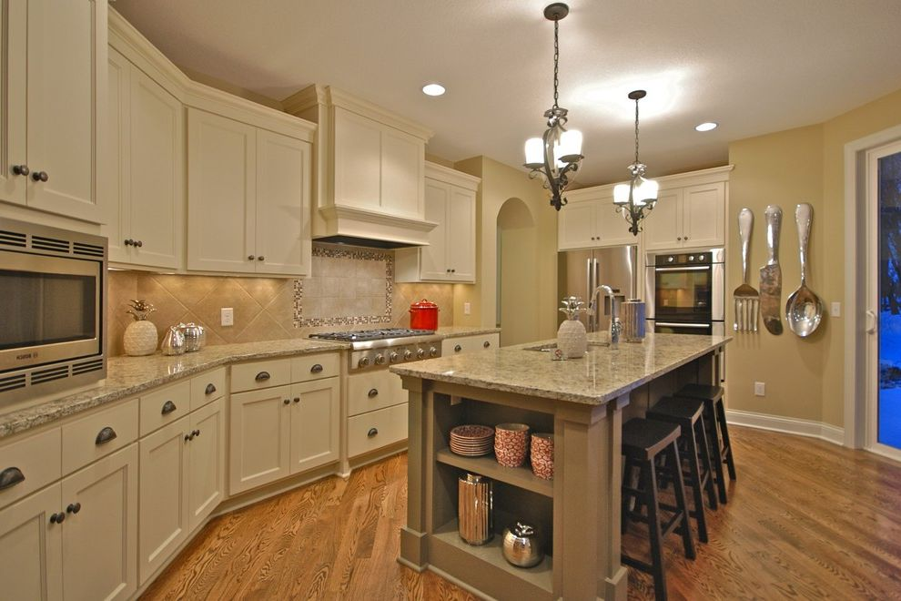 Sherwin Williams Fairfield   Traditional Kitchen Also Brass Counter Stools Drawer Pulls Frame and Panel Doors Granite Counter Oversized Cutlery Painted Cabinets Pendant Lights Silverware Art Stainless Appliances Tile Backsplash Wood Floor