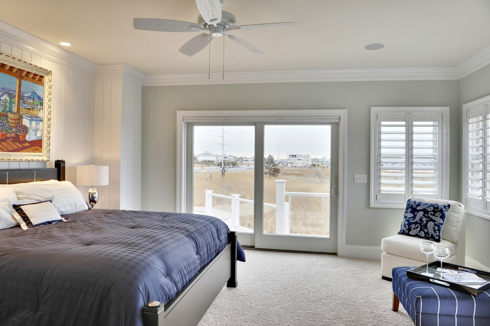 Sherwin Williams Fairfield with Beach Style Bedroom  and Accent Wall Baseboards Ceiling Fan Crown Molding Glass Doors Plantation Shutters Sliding Doors Slipper Chair View Wall Art Wall Decor White Wood Window Treatments Wood Bed Wood Paneling Wood Trim