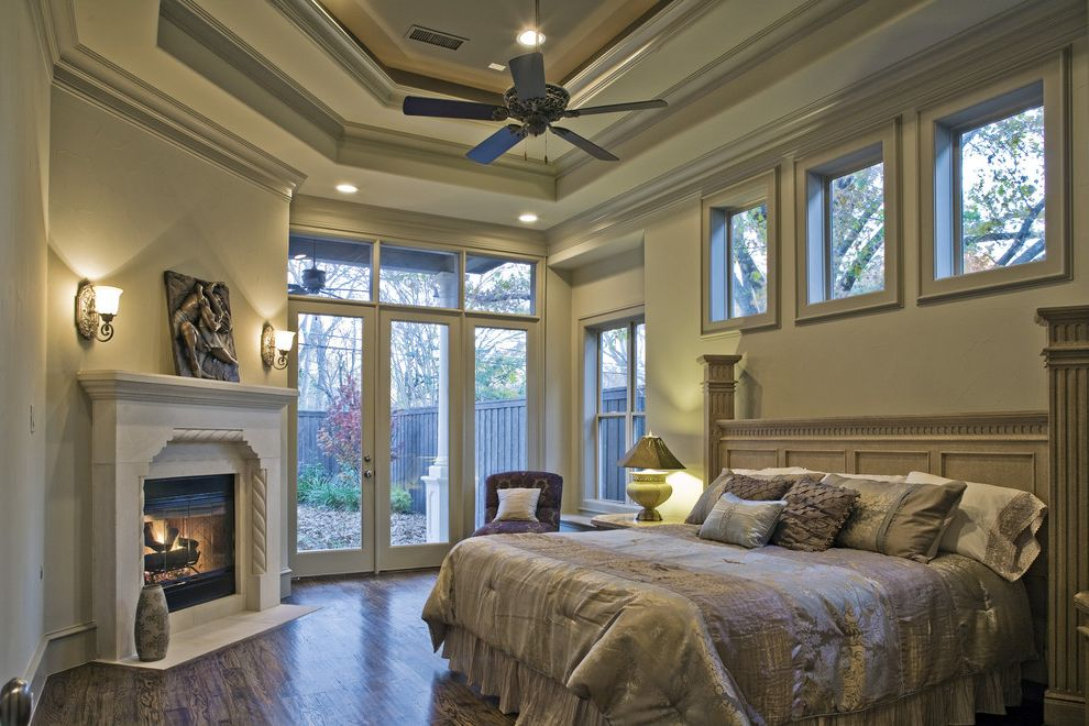 Sherwinn Williams with Mediterranean Bedroom  and Bed Skirt Beige Carved Stone Mantel Ceiling Fan Corner Fireplace Crown Molding Dentil Molding Fluted Wood Gray Patio Doors Tray Ceiling Wall Sconce Wood Floor