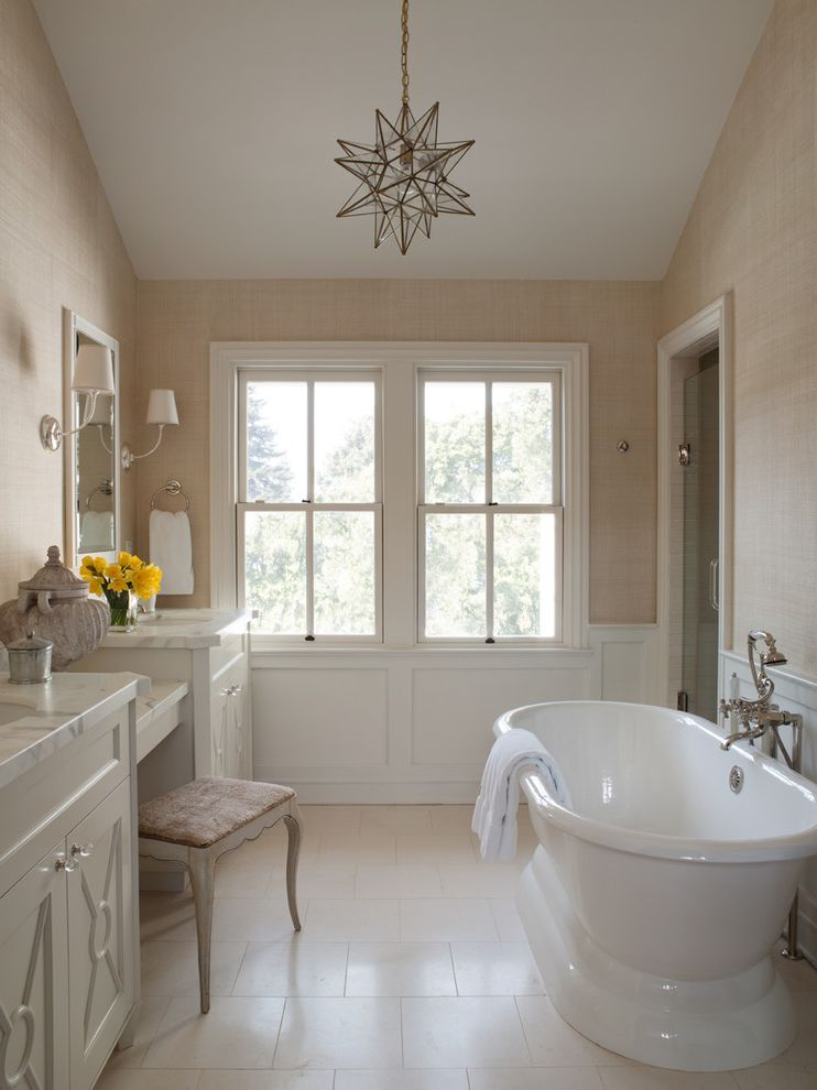 Soaker Tub Faucet with Traditional Bathroom and 2 Over 2 Windows Dressing Table Stool Free Standing Bathtub Glass Knobs Grass Cloth Marble Counter Moravian Star Light Nickel Wall Sconce Silver Wall Sconce Textured Wall White Tile Floor Window