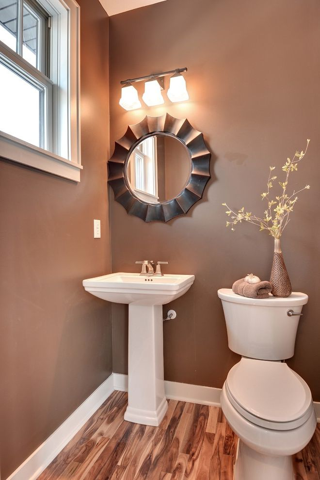 Southern Lights Mn   Transitional Powder Room  and Baseboard Hardwood Floor Pedestal Sink Round Mirror Sconce Small Bathroom Tan Wall Toilet Vase White Window Trim Window