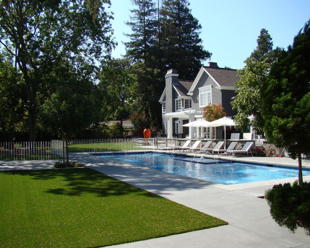 Straightforward Fence with Traditional Pool  and Acrylic Rods Chimney Concrete Gable Roof Lawn Lounge Chairs Orange Pot Pool Pool Deck Umbrellas