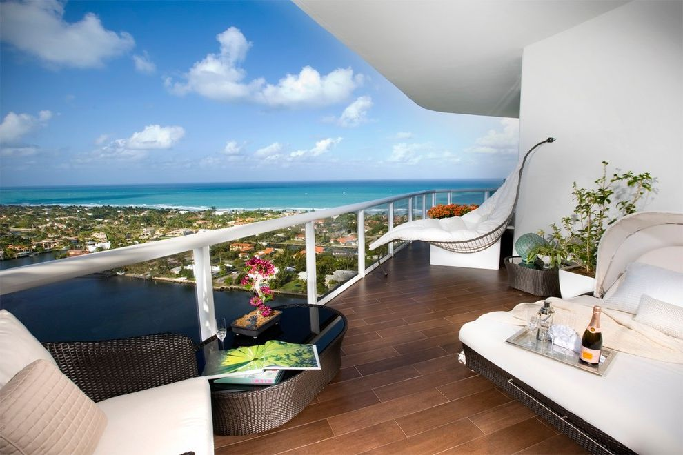 Sunny Designs Santa Fe Collection with Modern Balcony Also Balcony Beach Front Beach View Black Glass Overlay Blue Sky Clouds Hammock Chair Metal Railing Ocean View Potted Plants Waterfront White Interiors White Walls Wicker Ottoman