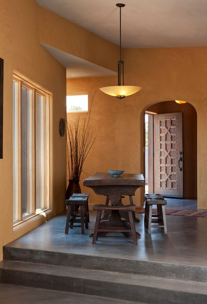 Superior Concrete Products   Southwestern Dining Room  and Arched Doorway Carved Door Concrete Floors Exotic Glass Pendant Light Glass Windows Global Ochre Shinto Chair Wood Table