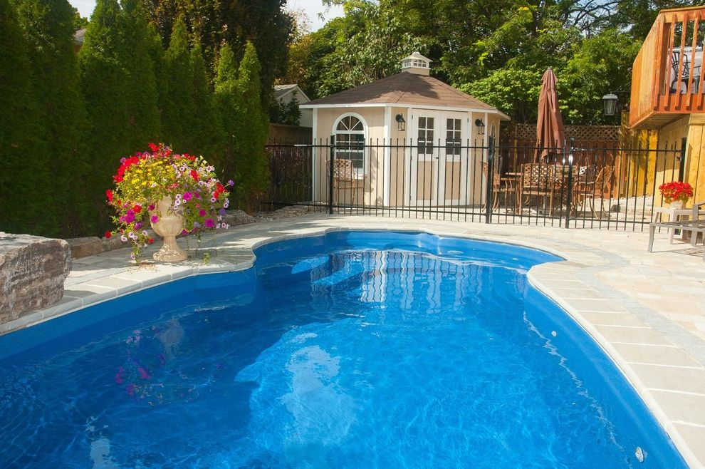Surfside Pools with  Pool  and Black Wrought Iron Fence Brown Patio Furniture Brown Patio Umbrella Customized Pool Pool House Potted Plants