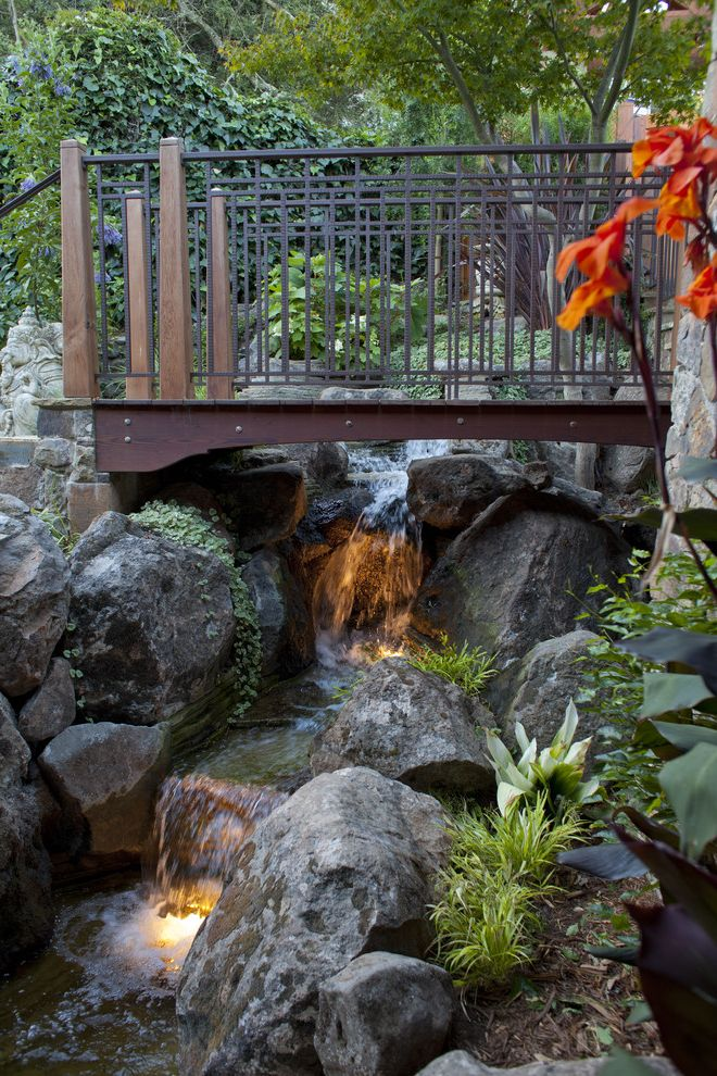Swedish Mill Creek with Tropical Landscape Also Boulders Bridge Creek Landscaping Metal Guardrail Metal Railing River Underwater Lighting Water Feature Waterfall Wood Bridge