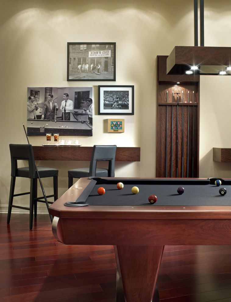 Table with Shelf Underneath with Contemporary Family Room  and Black and White Photography Black Leather Classic Movies Counter Stools Cue Rack Dark Stained Wood Floor Floating Shelf Game Room Pool Table White Walls