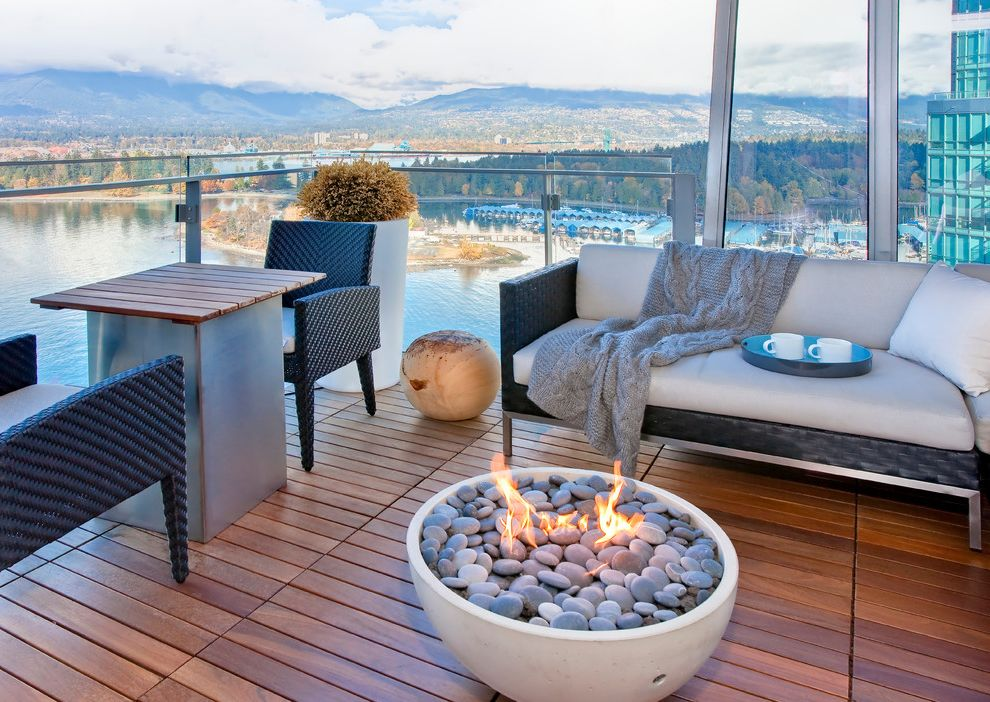 Tabletop Fire Bowl with Contemporary Balcony  and Fire Pit Glass Panel Railing Ipe Mountains Outdoor Seating Serving Tray Stones Tall Planter Water View White Seat Cushions Wood Ball Wood Deck Woven