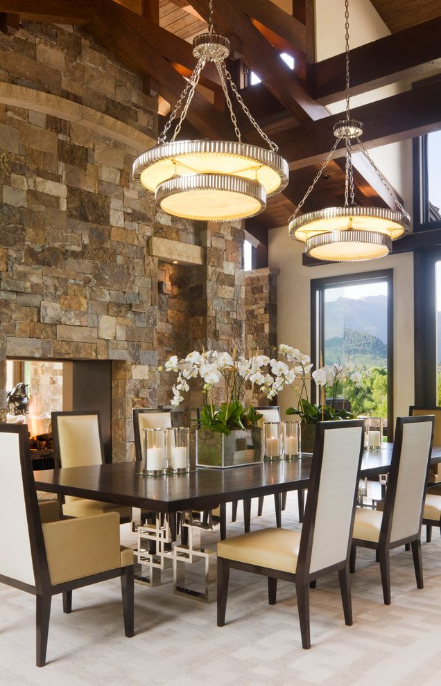 Tall Candle Pillars   Contemporary Dining Room  and Beams Chrome Dark Stained Wood Dark Stained Wood Beams Dining Room Large Dining Table Open Sided Fireplace Pendant Lights Stacked Stone Stone Fireplace Stone Wall Tall Ceilings Vaulted Ceiling View