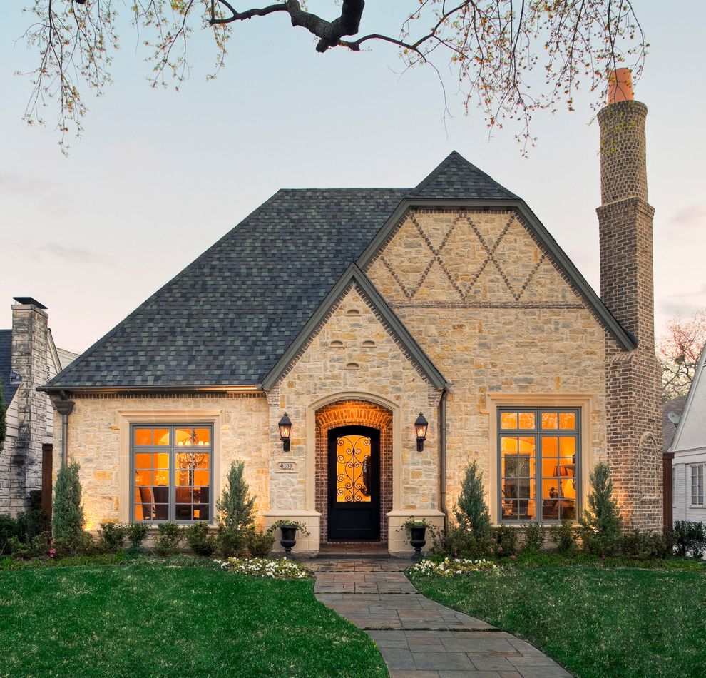 Tamko Heritage Shingles with Traditional Exterior  and Arched Door Brick Chimney Capped Gable Curb Appeal Diamond Pattern Dusk Filagree Front Approach Front Door Hip Roof Porch Light Red Brick Voussoirs Sidewalk Snow Guards Stone Wall Wall Lanterns