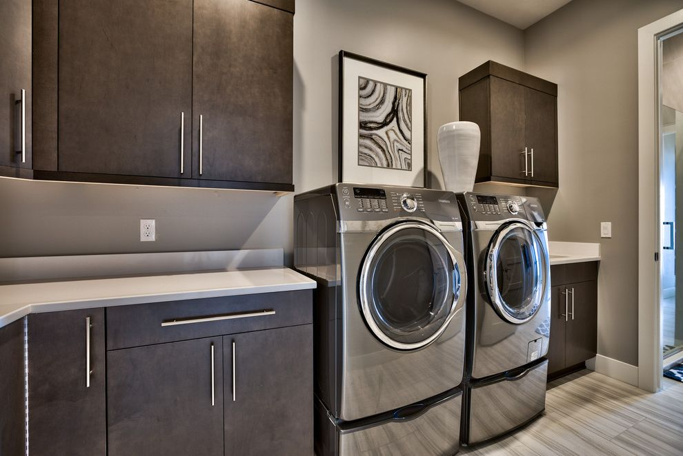 The Laundry Room Las Vegas with Contemporary Laundry Room Also Flat Panel Cabinets Gray Walls L Shape Cabinets Modern Side by Side Laundry Machines Updated Wall Art White Countertops White Vase