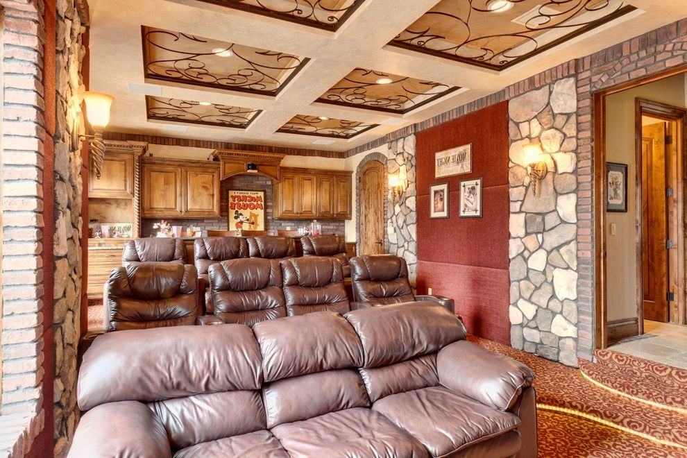 Theaters Springfield Mo   Mediterranean Home Theater  and Brick Brown Leather Seating Carpeting Coffered Ceiling Metal Scrollwork Movie Poster Raised Panel Cabinets Red Steps Stone Veneer Stone Walls Theater Room Wall Sconce