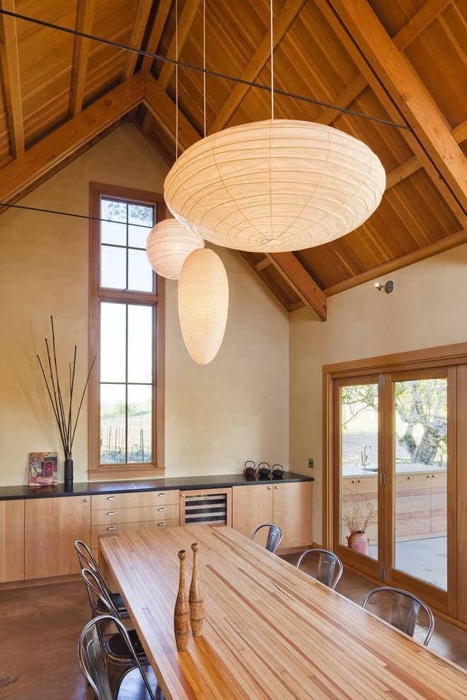 Thin Sheetrock   Farmhouse Dining Room Also Built in Storage Exposed Beams Lanterns Neutral Colors Patio Doors Sloped Ceiling Tolix Dining Chairs Vaulted Ceiling Wood Ceiling Wood Dining Table