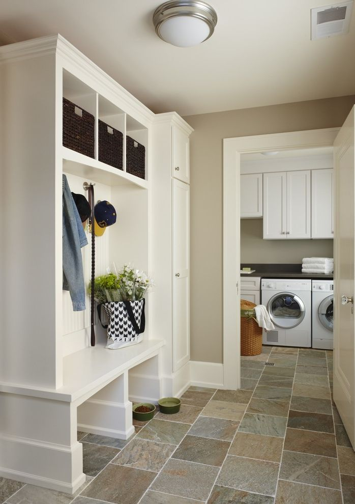 Thompson Building Supply   Traditional Laundry Room Also Beige Walls Built in Shelves Ceiling Lighting Flush Mount Sconce Front Loading Washer and Dryer Mudroom Stone Tile Floors Storage Cubbies White Trim