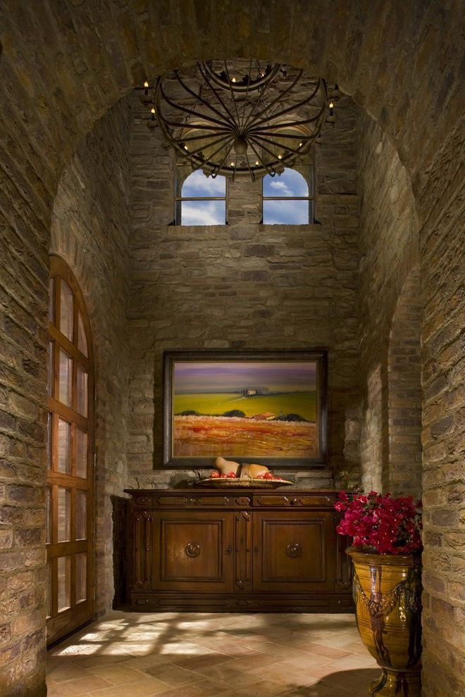 Toscana of Desert Ridge   Mediterranean Entry Also Arch Archway Commode Console High Ceiling Interior Landscape Painting Large Urn Stone Floor Stone Walls Vaulted Ceiling Wrought Iron Chandelier
