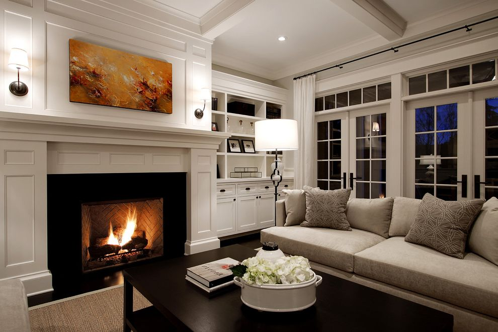 Town and Country Fireplaces with Traditional Living Room  and Coffee Table Coffered Ceiling Curtain Panels Dark Stained Wood Floor Fireplace French Doors Transom Windows Wall Sconce White Wood Surround Woven Area Rug Built in Bookshelves