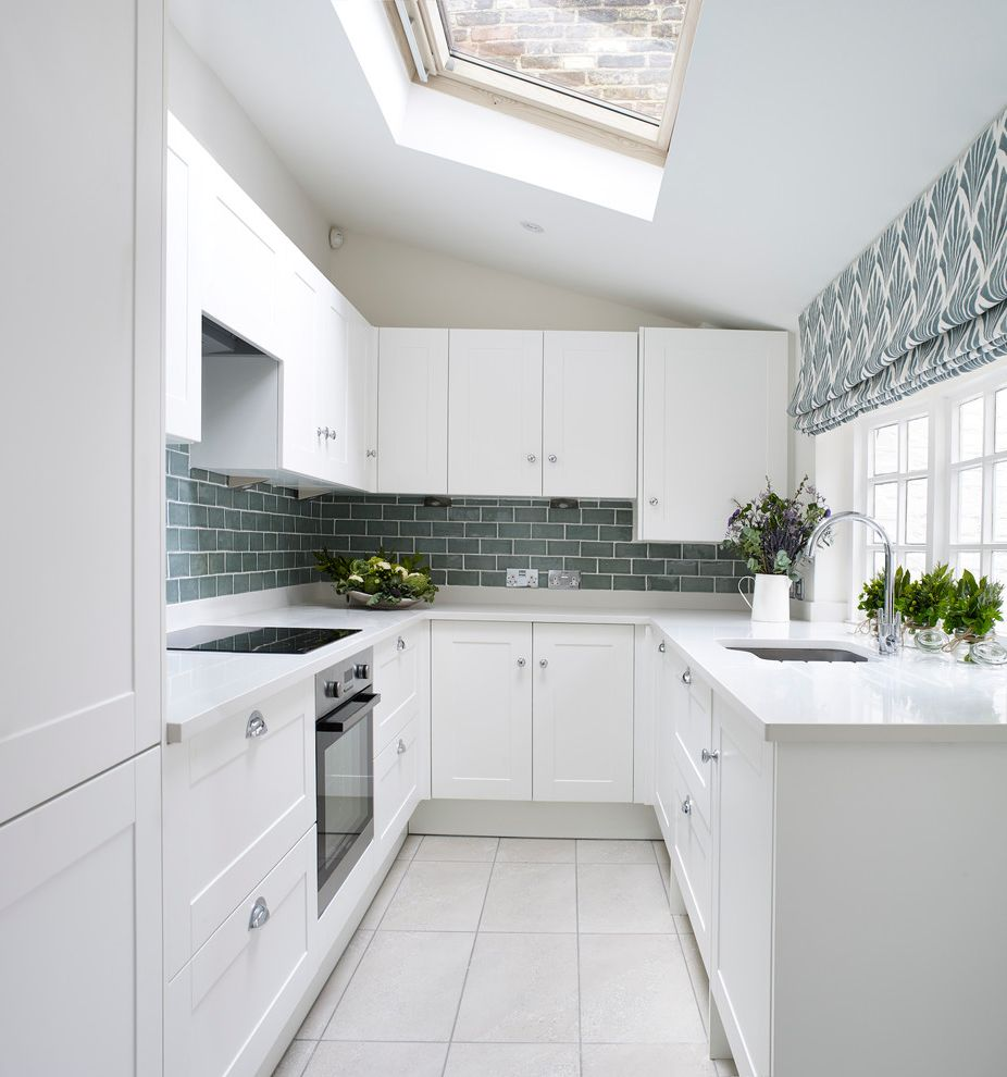 Trails of Shaker Run with Transitional Kitchen  and Blue Splashback Induction Cooktop Roman Shades Shaker Kitchen Sky Light Slanted Ceiling Small Kitchen Splashback Tile Splashback White Kitchen White Worktops