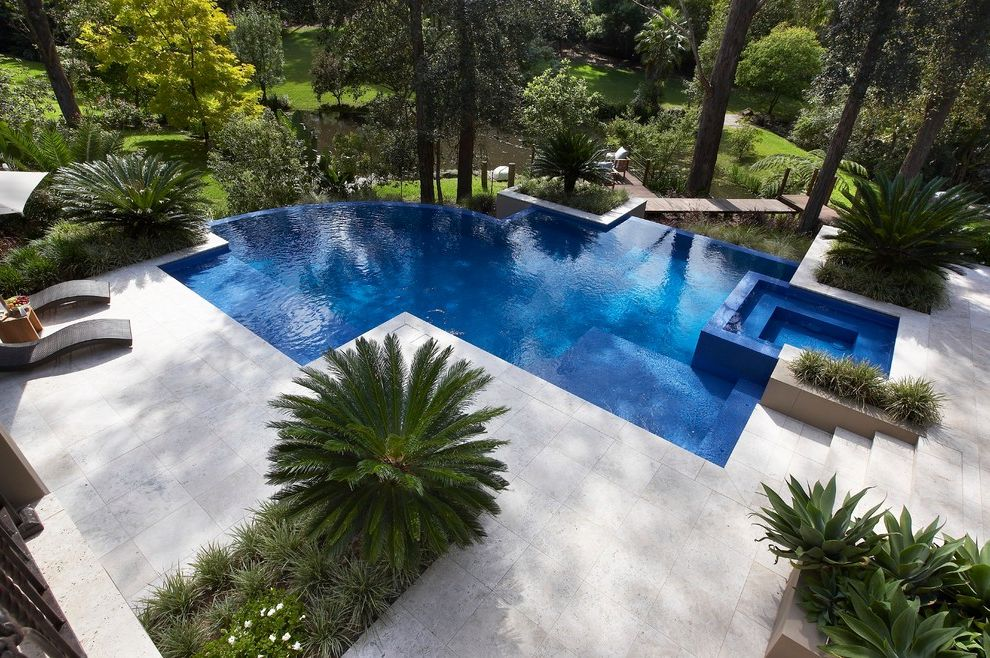 Travertine Tile Pros and Cons   Contemporary Pool  and Aquatic Hot Tub Infinity Edge Irregular Shape Pool Lounge Chairs Pavers Plants Spa Trees Water Feature