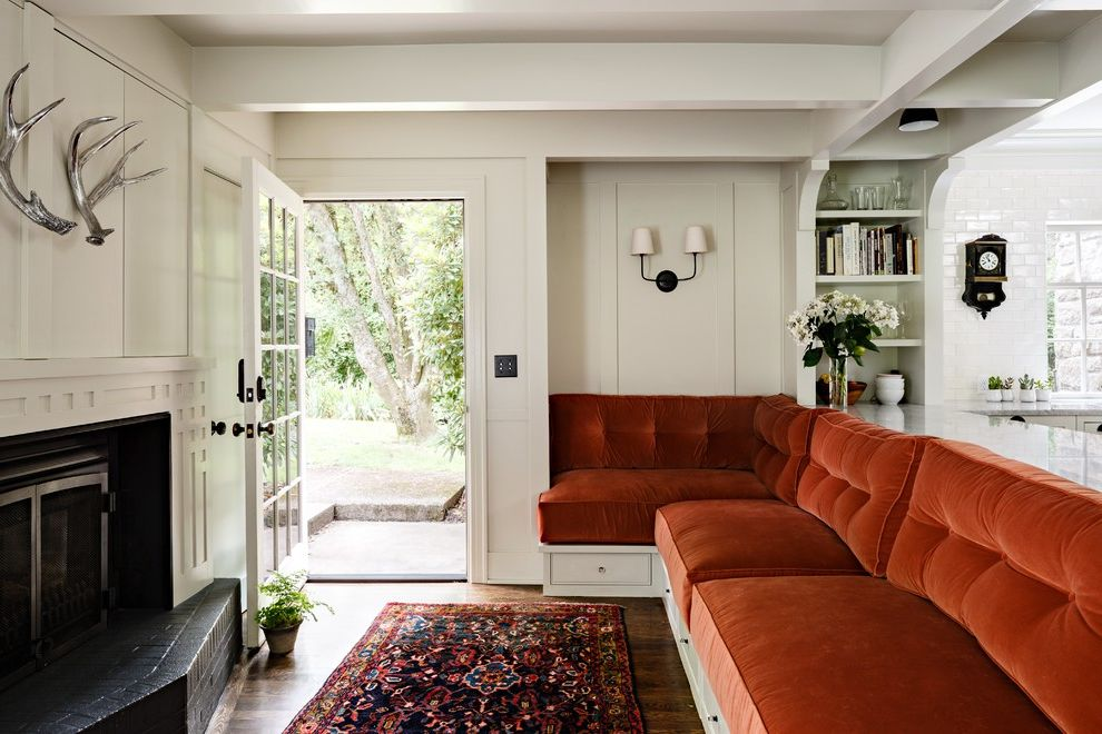 Tudor Definition with Transitional Family Room Also Beamed Ceiling Built in Bench Glass Door Open Shelves Orange Cushions Silver Antlers Wall Sconce