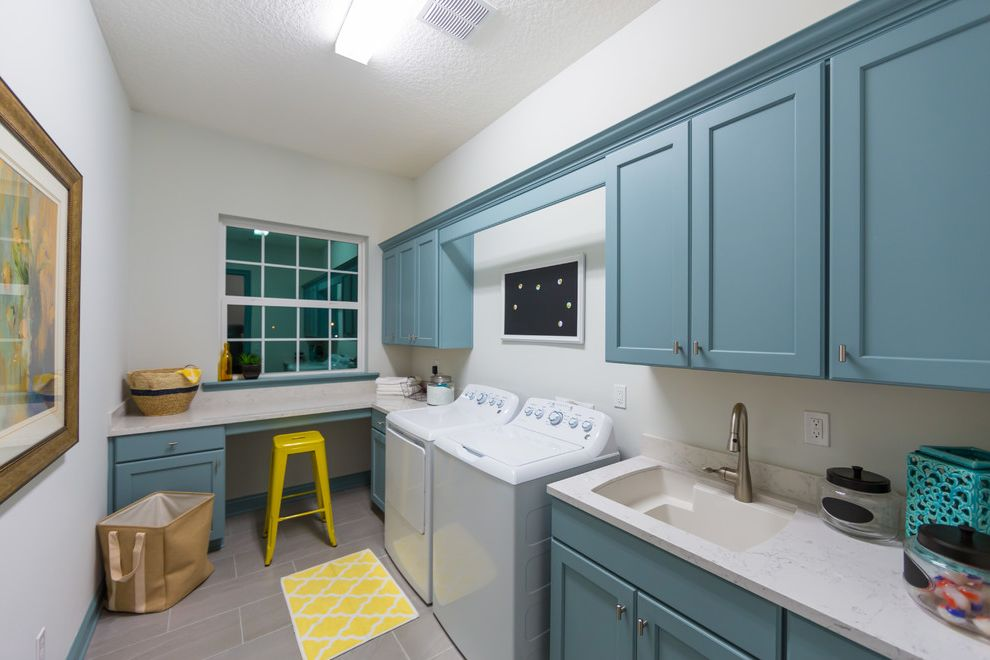 Twenty Mile Theater with Transitional Laundry Room  and Blue Shaker Cabinets Gray Floor Side by Side Washer and Dryer Undermount Sink White Walls Yellow Mat Yellow Stool
