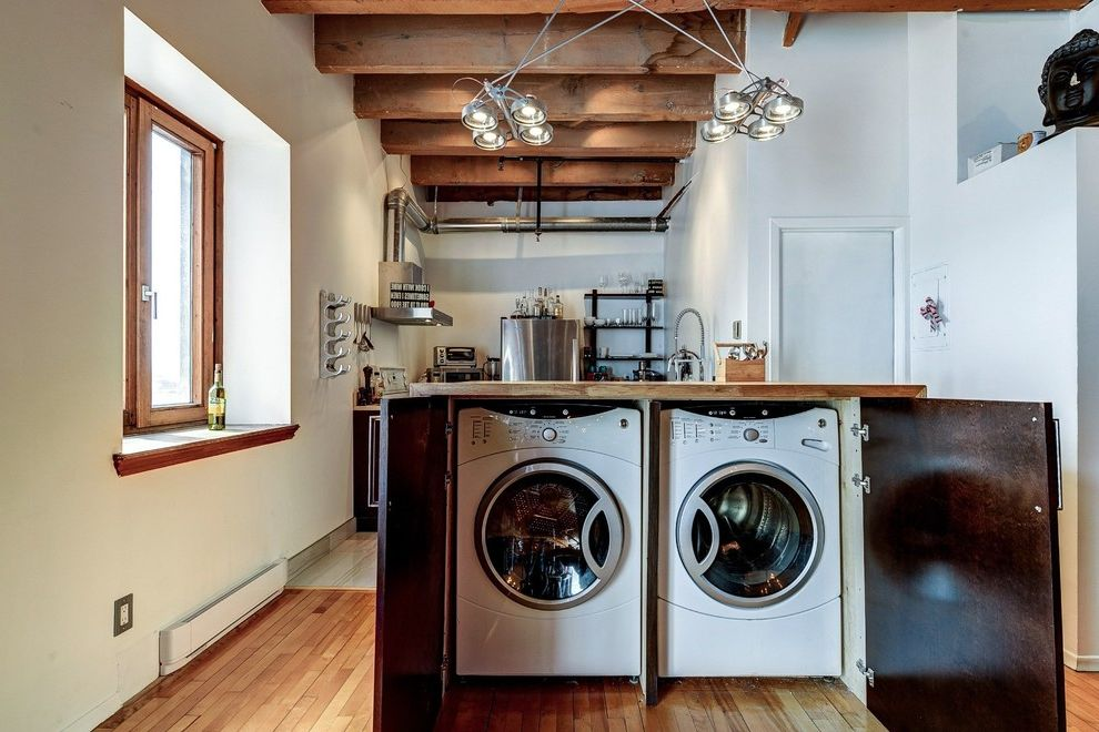 Under Counter Washer and Dryer with Industrial Laundry Room Also Converted Loft Exposed Wooden Beams Laundry in Kitchen Open Floor Plan Under Counter Laundry Wood Framed Windows Wooden Counter