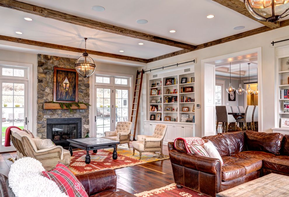 Victorian Hotel Pendant   Victorian Living Room  and Area Rug Distressed Leather Sofa Exposed Beams Exposed Stone Glass Pendants Hanging Glass Pendant Leather Couch Rolling Library Ladder Shelving Stone Wall Storage Tuffed Chairs