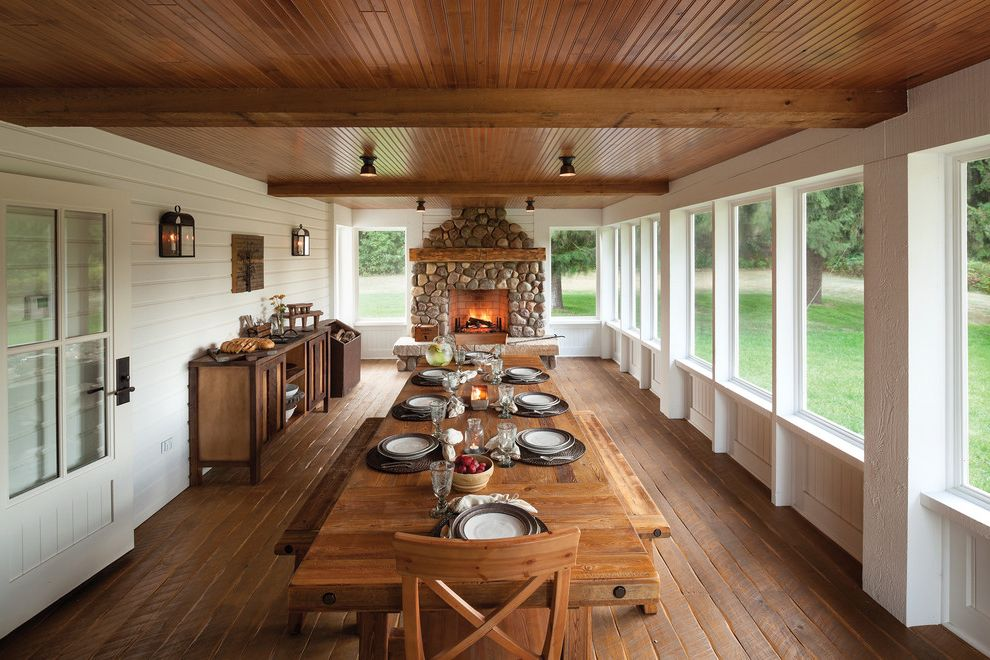 Viking Lumber with Farmhouse Porch Also Enclosed Porch Family Friendly Farm Farmhouse Table Large Dining Table Large Porch Long Dining Table Stone Fireplace Sunroom White Siding Wood Beams Wood Dining Bench Wood Dining Table Wood Floor