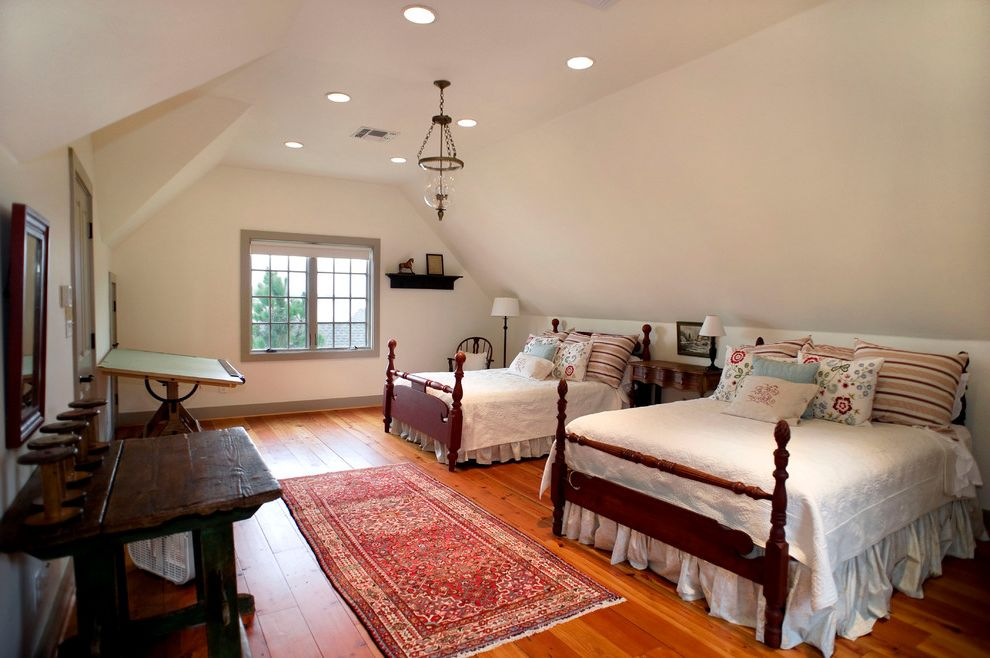 Walloon Lake Inn with Traditional Bedroom  and Antique Tables Bed Skirt Drafting Table Four Poster Beds Gray Painted Trim Hurricane Lantern Lake House Pendant Light Pillows Recessed Lights Red Area Rug Spools Vaulted Ceiling Wood Floor