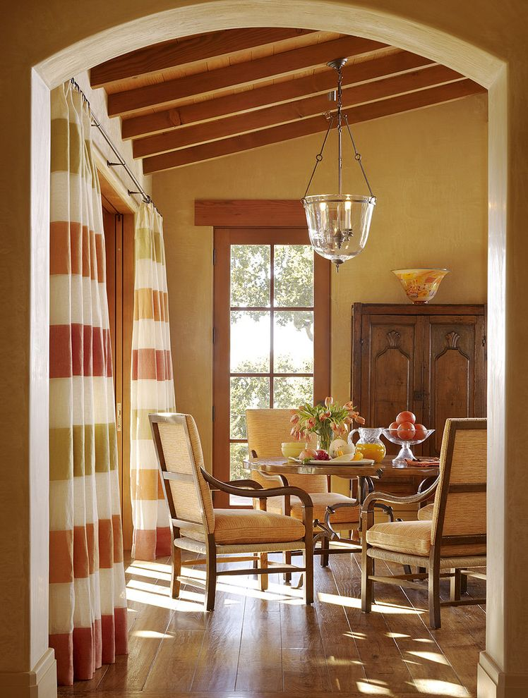 Warm Yellow Paint Colors   Mediterranean Dining Room  and Colorful Striped Curtains Glass Blown Bowl Pendant Light Upholstered Dining Chairs Warm Colors Wood Beams Wood Dining Table Wood Floor Wood Trim