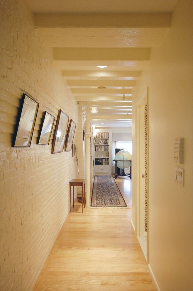 Warm Yellow Paint Colors with Rustic Hall  and Brick Wall Exposed Beams Gallery Wall Globe Neutral Colors Oriental Rug Painted Brick Rug Runner Rustic Wall Art Wall Decor White Brick Wood Flooring