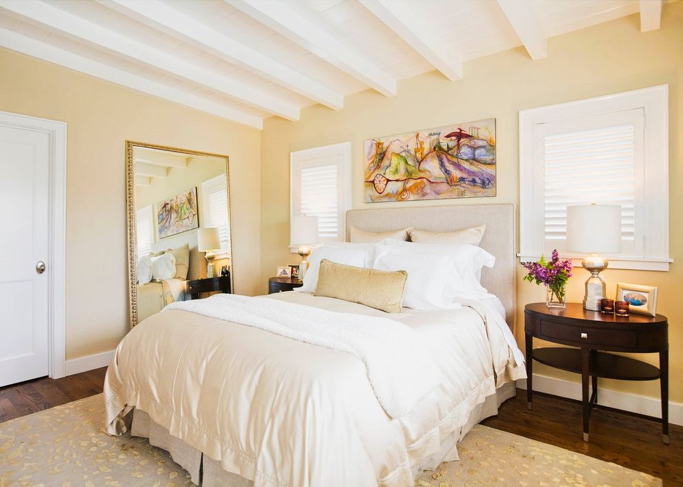 Warm Yellow Paint Colors with Traditional Bedroom  and Butter Yellow Walls Cream Duvet Exposed Beams Large Mirror Oval Nighstand Plantation Blinds Rafters Upholstered Headboard White Beams Yellow and Gray Rug