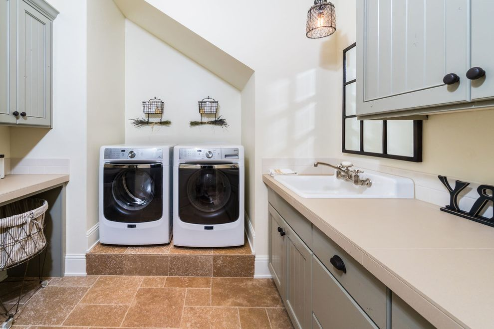 Washer and Dryer Platform   Farmhouse Laundry Room  and Beige Tile Drop in Sink Farmhouse Chic Gray Cabinets Louvered Cabinets Pendant Lighting Rustic Charm Side by Side Sloped Ceiling Traditional Travertine Wire Baskets