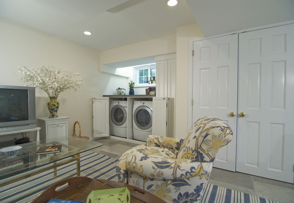 Washer and Dryer Platform   Traditional Basement Also Area Rug Ceiling Lighting Floral Armchair Front Loading Washer and Dryer Glass Coffee Table Laundry Room Neutral Colors Recessed Lighting Stripes Tile Flooring Upholstered Armchair