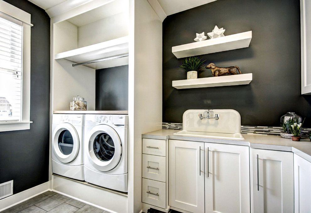 Washer and Dryer Platform with Traditional Laundry Room  and Black and White Black Painted Wall Blinds Built Ins Counter Floating Shelves Front Loading Washer Dryer Laundry Storage Nook Shaker Panel Cabinets Sink Tile Floor White Window Casing Window