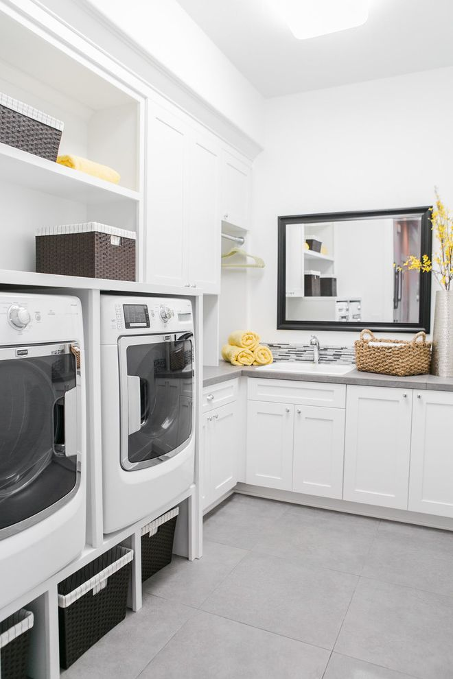 Washer and Dryer Platform with Transitional Laundry Room Also Frame Mirror Gray Countertop Gray Tile Floor Open Shelves Storage Baskets Yellow Accents
