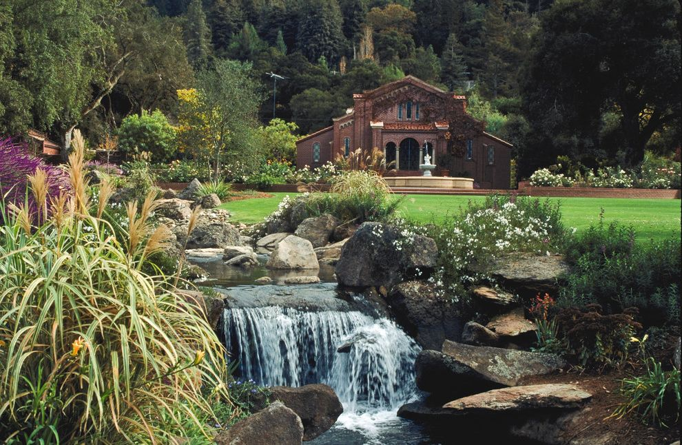 Water Gardens Theater with Traditional Landscape Also Boulders Brick Wall Fountain Grass Large Lawn Lawn Oversized Lawn Purple Flowers Red Exterior Red Siding Rock Landscape Tall Grass Water Feature Water Fountain Waterfall White Flowers