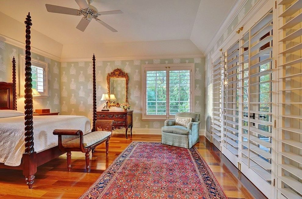 What Are Plantation Shutters   Tropical Bedroom Also Bedroom Bench Ceiling Fan Four Poster Bed Gold Mirror Green Armchair Light Green Wallpaper Patterned Wallpaper Traditional Traditional Area Rug White Molding White Plantation Shutters White Trim