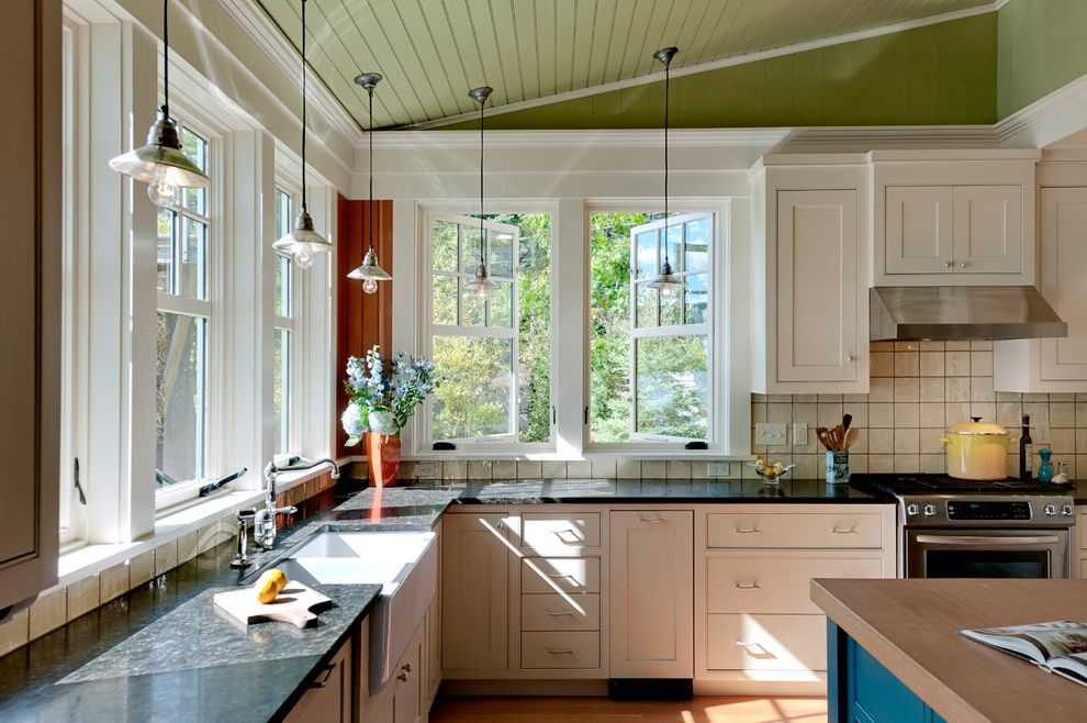 What is a Casement Window   Rustic Kitchen  and Apron Sink Beadboard Ceiling Farm Sink Frame and Panel Woodwork Granite Counters Green Ceiling Kitchen Island Lake House Pendant Lights Stainless Steel Appliances Summer Home White Cabinets Wood Counter