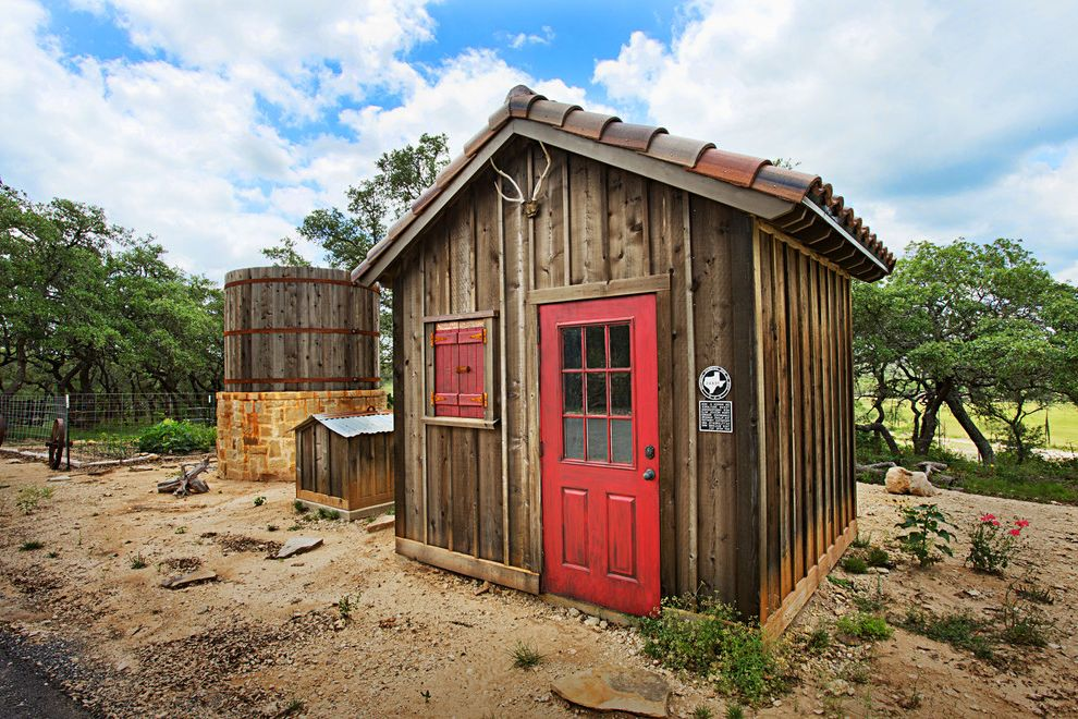 What is a Cistern with Mediterranean Shed  and Antlers Clay Tile Roof Red Door Red Window Shutters Rustic Wood Siding