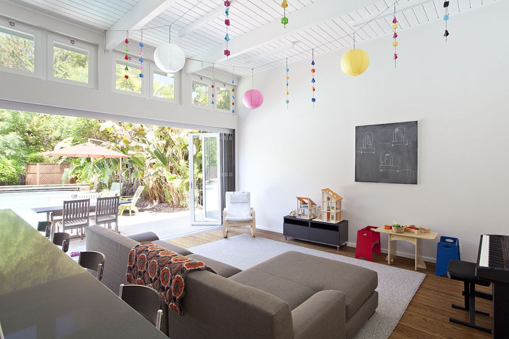 What is a Family Room   Midcentury Family Room Also Chalkboard Clerestory Exposed Beams Folding Doors Gray Couch Indoor Outdoor Nanawall Neutral Colors Painted Wood Playroom Post and Beam Ranch Sectional White Wood Wood Ceiling Wood Flooring