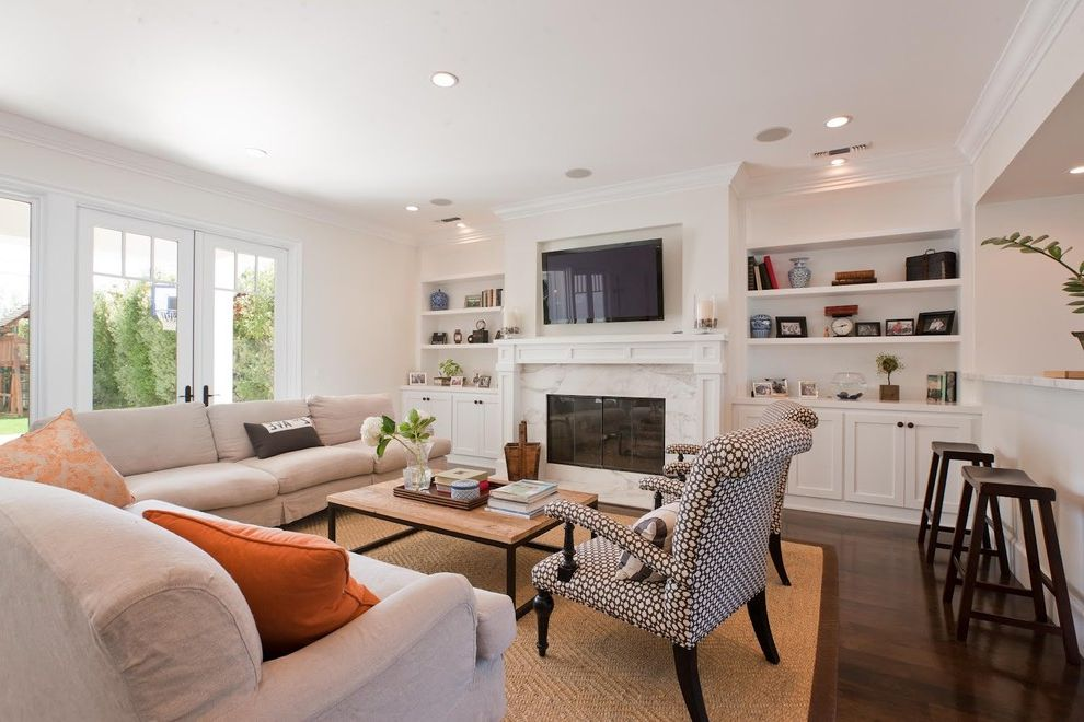 What is a Family Room   Traditional Family Room Also Beige Couch Built in Cupboards Built in Shelves Crown Molding Family Room Fireplace French Doors Hickory Floor Jute Rug Neutral Palette Patterned Accent Chairs Wall Mounted Tv White Built Ins