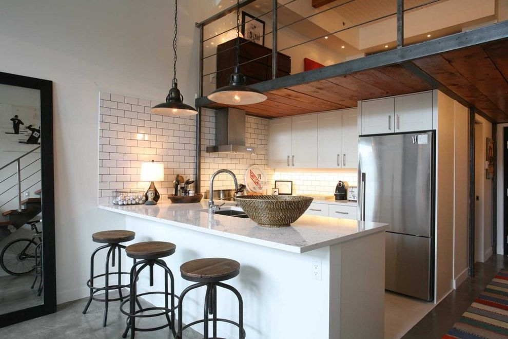 What is a Loft Apartment with Industrial Kitchen  and Balcony Floor Mirror High Ceilings Kitchen Peninsula Loft Loft Apartment Metal Railing Pendant Lights Peninsula Peninsula Sink Small Kitchen Swivel Stools White Counter
