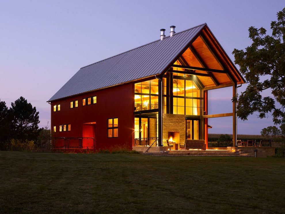 What is a Pole Barn with Farmhouse Exterior  and Backyard Barn Exposed Beams Farm House Field Glass Wall Metal Roof Modern Barn Outdoor Fireplace Red Barn Red House Standing Seam Roof Stone Wall Sustainable