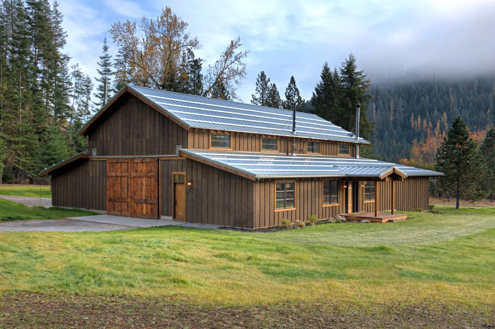 What is a Pole Barn with Rustic Exterior  and Awning Barn Style Dark Wood Exterior Dark Wood Siding Driveway Large Barn Doors Metal Roof Outside Lighting Pathway Plants Ranch Timber Wood Deck Wood Posts