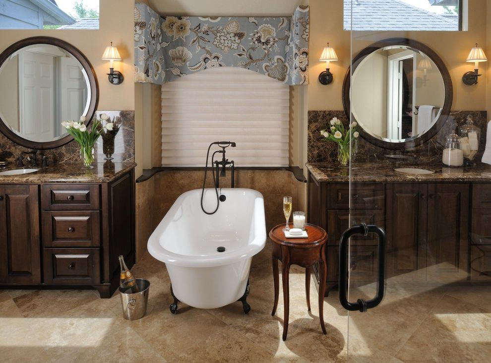 What is a Roman Tub with Traditional Bathroom  and Alcove Bathroom Mirror Claw Foot Tub Clerestory Dark Wood Cabinets Double Sinks Double Vanity Floral Arrangement Nook Round Mirror Sconce Valance Wall Lighting Window Treatments