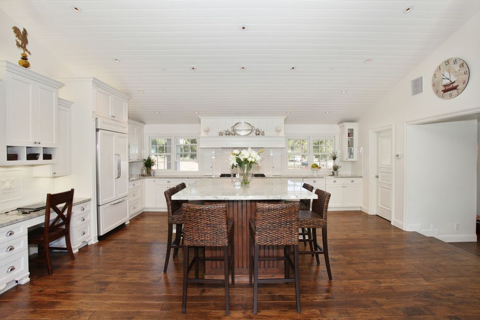 What is Engineered Hardwood with Traditional Kitchen  and Dark Stained Wood Desk Area Integrated Kitchen Kitchen Island Vaulted Ceiling White Tongue and Groove Ceiling Wood Floor Workstation Woven Counter Stools