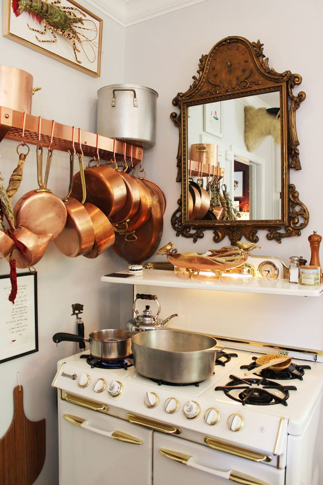 What is He Detergent with Traditional Kitchen  and Antique Copper Pots Gilded Mirror Gold Ledge Pot Rack Vintage Stove White Stove White Walls