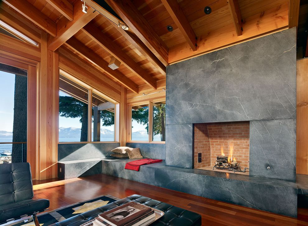 What is Soapstone   Contemporary Living Room  and Cabin Corner Windows Dark Wood Floors Exposed Beams Fireplace Hearth Lodge Rafters Raised Hearth Fireplace Sloped Ceiling Stone Bench Stone Slab Fireplace Surround Vaulted Ceiling Window Seat Wood Ceiling