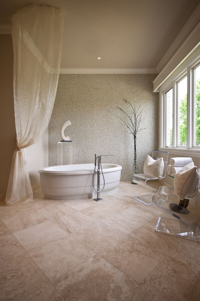 What is Travertine Tile with Contemporary Bathroom  and Accent Wall Clear Furniture Crown Molding Curtains Drapes Freestanding Tub Ghost Chair Monochromatic Neutral Colors Tile Flooring Translucent Chairs